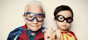 Man with white hair in clear goggles and blue cape raises fist, as does his young male sidekick in goggles and red cape.